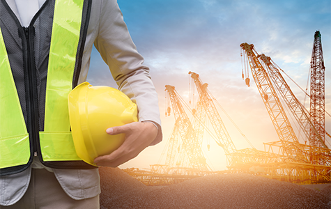 man on building site with helmet and cranes